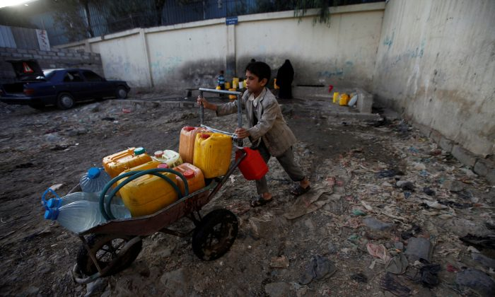 A boy pushes a wheelbarrow filled with water containers after collecting drinking water from a charity tap, amid a cholera outbreak, in Sanaa, Yemen on Oct.13, 2017. (Mohamed al-Sayaghi/Reuters)