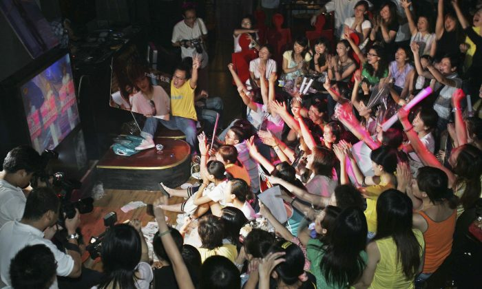"Fans of the TV Show ""Super Girl Voice"" watch and cheer for their favorite contestants at a bar on Aug. 26, 2005 in Shanghai, China. (China Photos/Getty Images)"