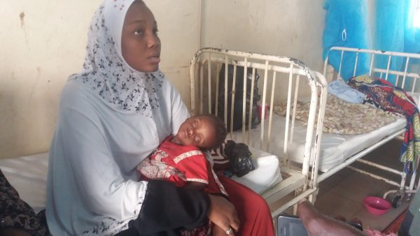 A woman holds her sick child as she waits for a doctor in Nigeria.