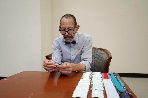 Gregory Bruce examining fabric