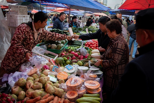 A vendor (L) sells vegetables to a customer at a market in Beijing on Oct. 16, 2018. (Nicolas ASFOURI / AFP/Getty Images)