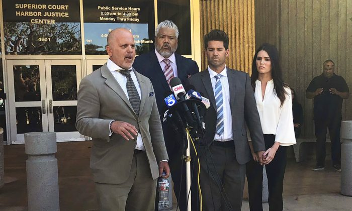 Reality show doctor Grant Robicheaux, second from right, and his girlfriend Cerissa Riley, right, listen as Robicheaux's attorney Philip Cohen, left, speaks outside court in Newport Beach, Calif., following their hearing on new criminal charges involving five additional victims on Oct. 17, 2018. (Amy Taxin/The Associated Press)