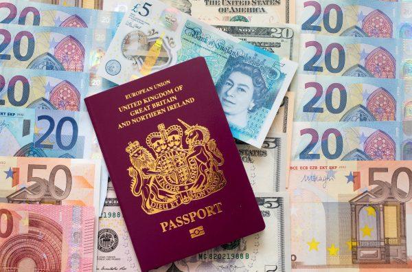 euro dollar and pound notes lie beside UK passport
