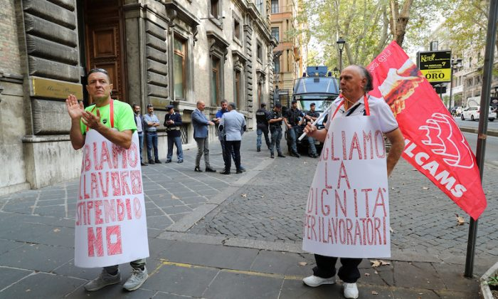 "People wearing signs that read ""We want dignity for workers"" (R) and ""We have work but no salary""  protest in front of the Italian Ministry of Labour office in Rome, Italy, Oct. 16, 2018. (Reuters/Tony Gentile"