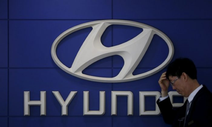 A car dealer stands in front of the logo of Hyundai Motor at its dealership in Seoul, South Korea, April 25, 2016. (REUTERS/Kim Hong-Ji/File Photo)