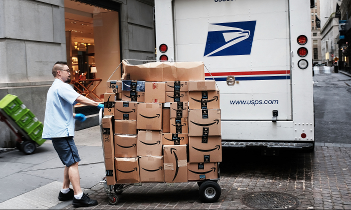 A US Postal worker delivers Amazon boxes outside of the New York Stock Exchange (NYSE) in New York City on Oct. 11, 2018. (Spencer Platt/Getty Images)