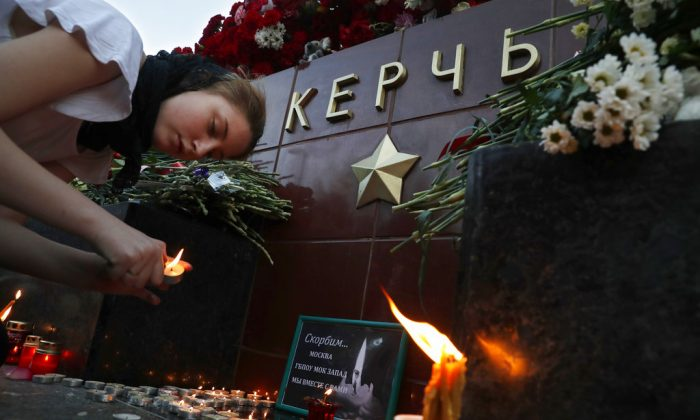 A girl lights a candle in memory of the victims of Wednesday's attack on a vocational college in Kerch, Crimea, at the memorial stone with the word Kerch in the Alexander Garden near the Kremlin, Moscow, Russia, Oct. 18, 2018. (AP Photo/Pavel Golovkin)