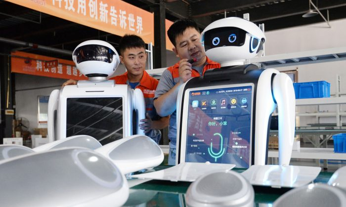 Employees assemble robots at a factory in Handan, Hebei Province, China on Aug. 27, 2018. (STR/AFP/Getty Images)