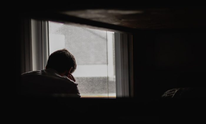 "File photo of a man looking out of a window. A group of girls in a Pennsylvania high school reportedly lied when they accused a male teen of sexual assault on two occasions, according to a lawsuit filed Oct. 1, 2018, that dubbed the female students ""mean girls."" (Unsplash/Andrik Langfield)"