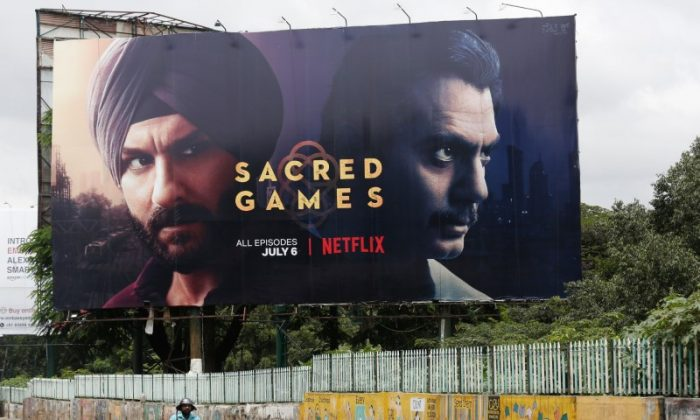"""A man rides his scooter past a hoardings of Netflix's new television series """"Sacred Games"""" in Bengaluru, India, on July 11, 2018. REUTERS/Abhishek N. Chinnappa"""