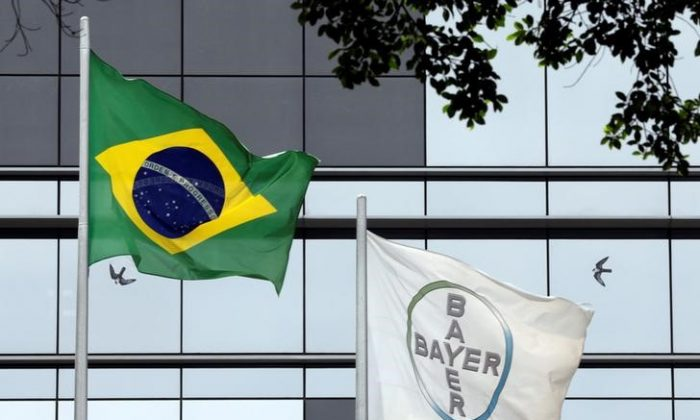 The Brazilian national flag is seen next to Bayer's flag in front of Bayer headquarters in Sao Paulo, Brazil, on Oct. 4, 2017. REUTERS/Paulo Whitaker