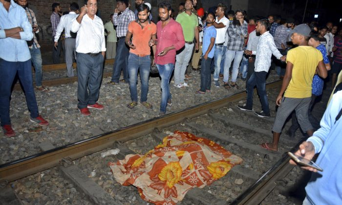 The body of a victim of a train accident lies covered in cloth on a railway track in Amritsar, India, on Oct. 19, 2018. (AP Photo/Prabhjot Gill)