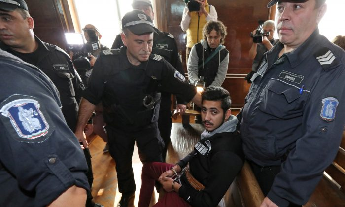 Police stand guard next to Severin Krasimirov, 21, who was arrested in Germany over the killing of TV journalist Viktoria Marinova, during his first appearance in court in Ruse, Bulgaria, on Oct. 19, 2018. (Stringer/Reuters)