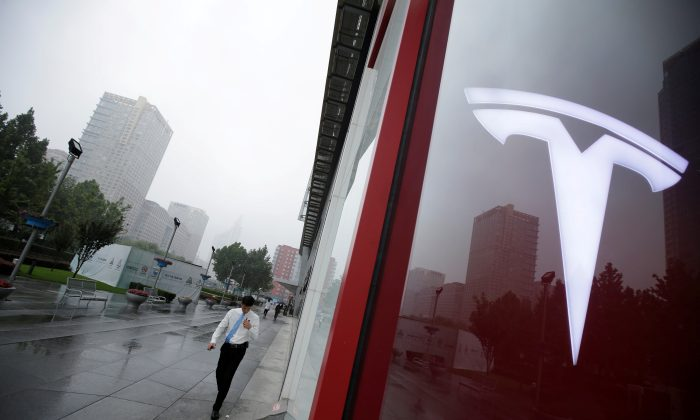 A man walks near a logo of Tesla outside its China headquarters at China Central Mall in Beijing, China Jul. 11, 2018. (Reuters/Jason Lee)