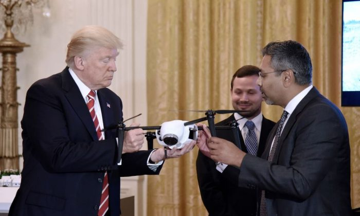 President Donald Trump holds a drone as George Mathew CEO & Chairman of Kespry explains how it works during  the American Leadership in Emerging Technology Event in the East Room of the White House in Washington, June 22, 2017 (Olivier Douliery-Pool/Getty Images)