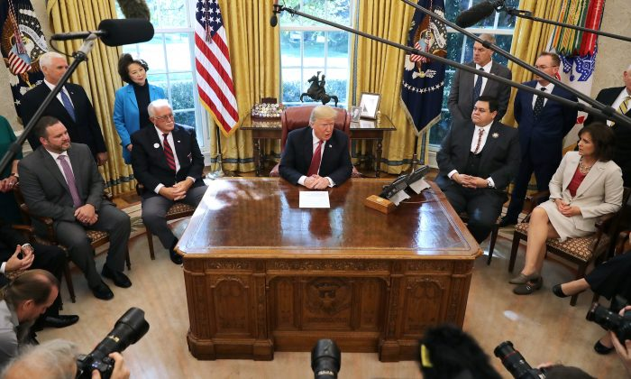 President Donald Trump (C) talks to journalists in the Oval Office at the White House, on Oct. 17, 2018. (Chip Somodevilla/Getty Images)