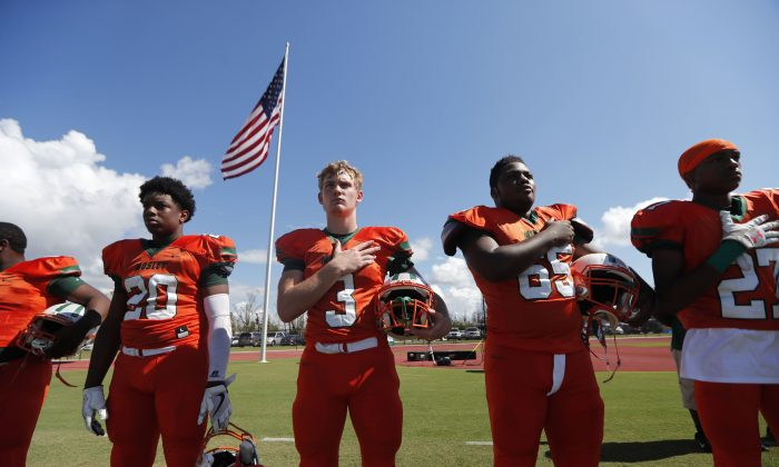 Mosley High football players hold their hands to their heart during the the national anthem, before the start of their football game against Pensacola, in the aftermath of Hurricane Michael in Panama City, Fla.,, Oct. 20, 2018. (AP Photo/Gerald Herber