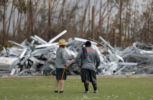Mosley High defensive coordinator Danny Nagy, left, and defensive line coach William Mosley, survey damage