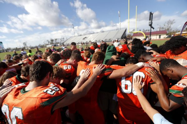 Coaches and players from Mosley High pray together