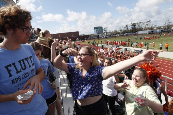 People attend and cheer the football game