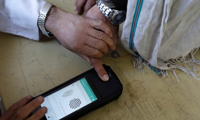 An election official scans a voter's finger with a biometric device at a polling station during a parliamentary election in Kabul, Afghanistan, Oct. 20, 2018. (Mohammad Ismail/Reuters)