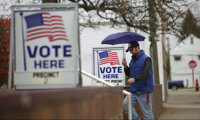 A man fills walks past voting signs displayed outside a polling station during the mid-term elections in Hamtramck, Michigan, in this  Nov. 4, 2014 file photo. (Joshua Lott/Getty Images)