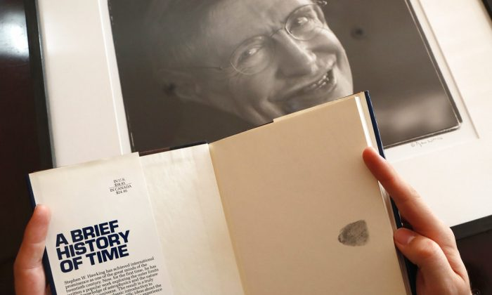 A Book, signed with a thumb print by Stephen Hawking is one of the personal and academic possessions of Stephen Hawking, photo behind, at the auction house Christies in London on Oct. 19, 2018. (AP Photo/Frank Augstein)