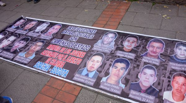 A banner showing the faces of a few of the young men who lost their lives.