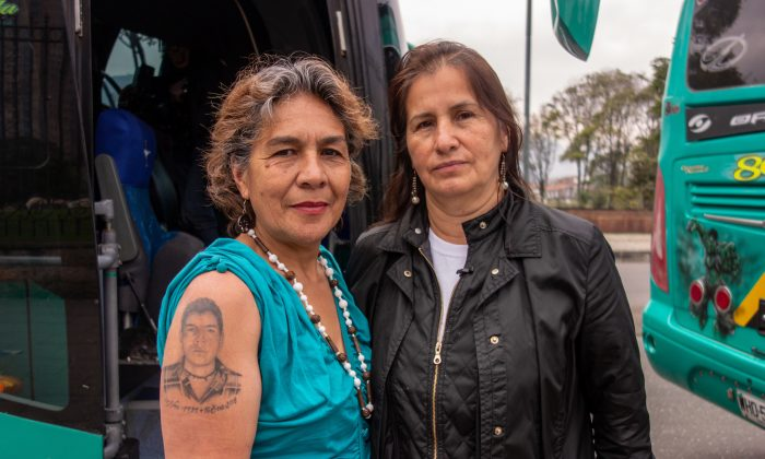 """María Doris Tejada (L), showing a tattoo of her missing son on her arm, and Jacqueline Castillo, the legal representative of Madres de Soacha, or Mothers of Soacha, who lost her brother in the phenomenon most commonly known as the """"false positives"""" scandal, pose for a photo on Oct. 13, 2018, in Bogota, Colombia, before going on a 16-hour bus ride to the other side of the country to commemorate their loved ones who lost their lives in the scandal.  (Luke Taylor/Special to The Epoch Times)"""