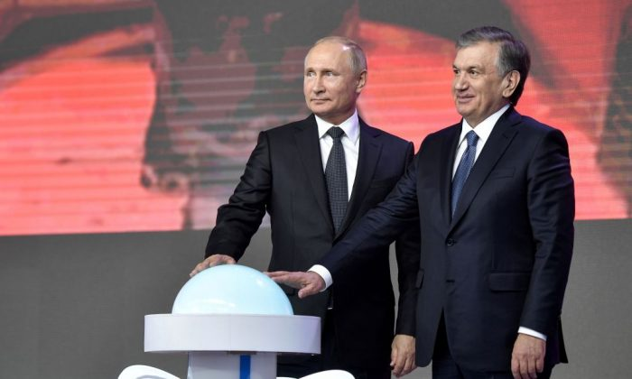Russian President Vladimir Putin (L) and President of Uzbekistan Shavkat Mirziyoyev, inaugurate the construction of the first nuclear power plant, during a forum of inter-regional cooperation between Russia and Uzbekistan in Tashkent on Oct. 19, 2018. (Alexey Nikolsky/AFP/Getty Images)