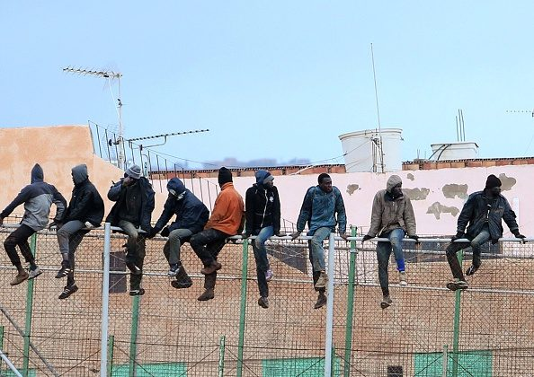 Would-be immigrants sit atop a border fence separating Morocco from the north African Spanish enclave of Melilla on Feb.19, 2015. (Angela Rios/AFP/Getty Images)