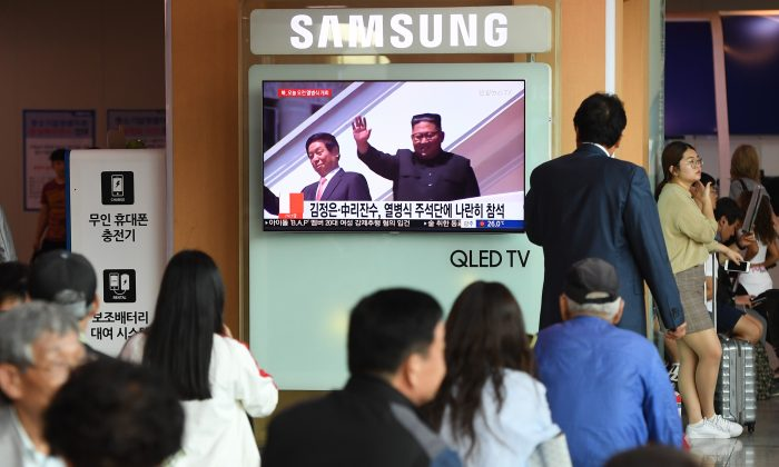 People watch a television news reporting a parade marking the 70th anniversary of the foundation of North Korea held in Pyongyang and showing North Korean leader Kim Jong-Un (R) and China's Chairman of the Standing Committee of the National People's Congress Li Zhanshu (L), at a railway station in Seoul on Sept. 9, 2018. (Jung Yeon-je/AFP/Getty Images)
