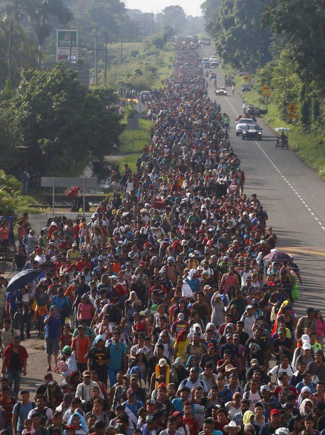 migrant caravan walks on road