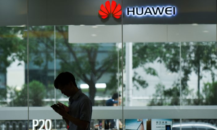 A man uses his mobile phone outside a Huawei store in Beijing on August 7, 2018. (WANG ZHAO/AFP/Getty Images)