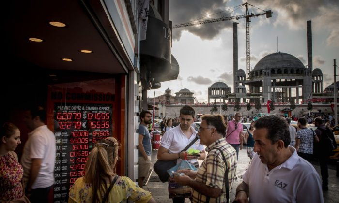 People wait to change money at a currency exchange office in front of the underconstruction, Taksim Square Mosque on Aug. 29, 2018 in Istanbul, Turkey. (Chris McGrath/Getty Images)