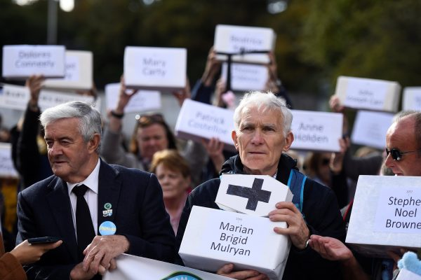 Peter Mulryan holds a funeral box representing a dead child
