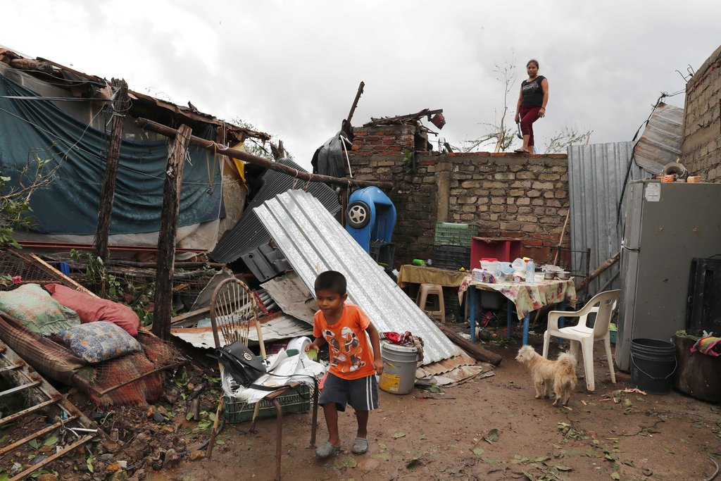 Boy walks near damaged home