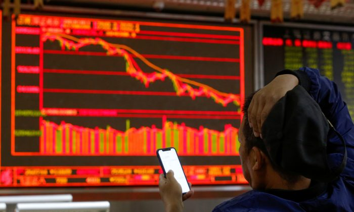 An investor sits in front of displays showing stock information at a brokerage office in Beijing on Oct. 11, 2018. (Thomas Peter/Reuters)