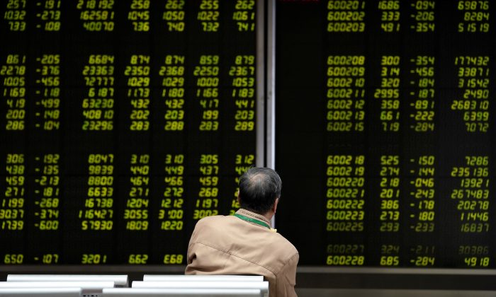 An investor watches a board showing stock information at a brokerage office in Beijing on Oct. 8, 2018. (Jason Lee/Reuters)
