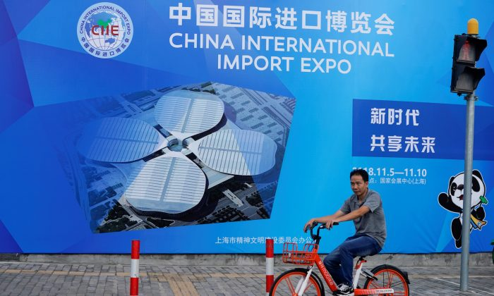 A man rides a bicycle near a billboard promoting the upcoming China International Import Expo in Shanghai, China  on Sept. 27, 2018. (Aly Song/Reuters)