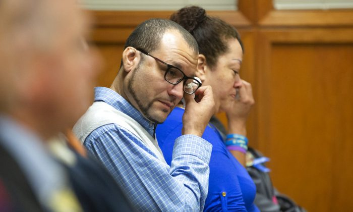 Carlo Brewer wipes away tears after Stephen Bodine was found guilty on all charges Wednesday, Oct. 24,, 2018, in Wichita, Kan., in connection with the murder of his three-year-old son Evan Brewer. (Travis Heying/The Wichita Eagle via AP)