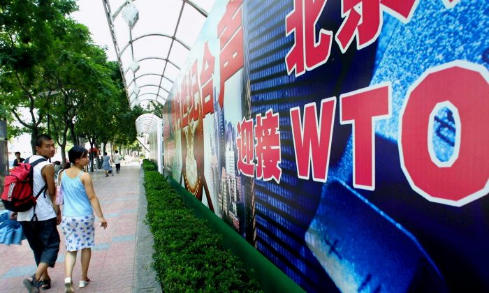 A young Chinese couple walk by a billboard promoting China's membership to the World Trade Organization (WTO), along a street in Beijing on July 17, 2001. (GOH CHAI HIN/AFP/Getty Images)