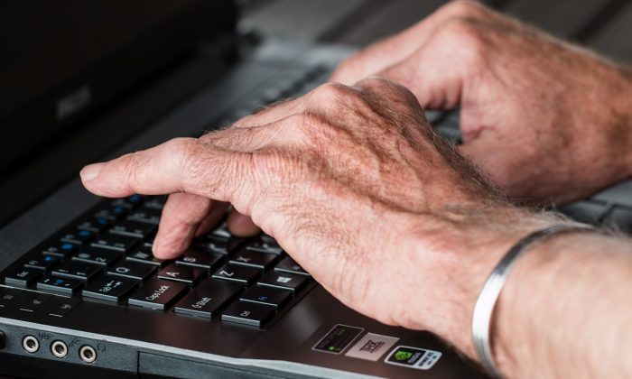 Old hands typing on laptop. (Pixabay)