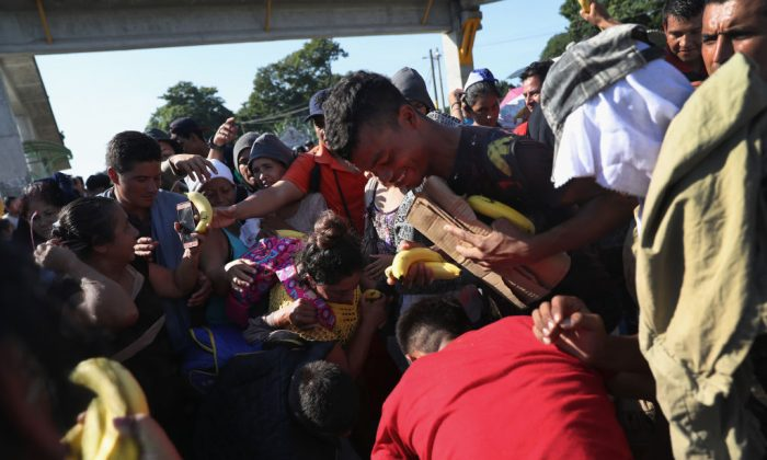 Immigrants scramble for fresh fruit given out by local residents after the migrant caravan crossed into Mexico from the Guatemalan border on Oct. 21, 2018 near Ciudad Hidalgo, Mexico. (John Moore/Getty Images)