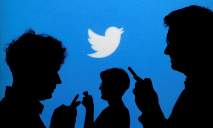 People holding mobile phones are silhouetted against a backdrop projected with the Twitter logo in this illustration picture taken in  Warsaw on Sept. 27, 2013.   (Kacper Pempel/Illustration/File Photo/Reuters)