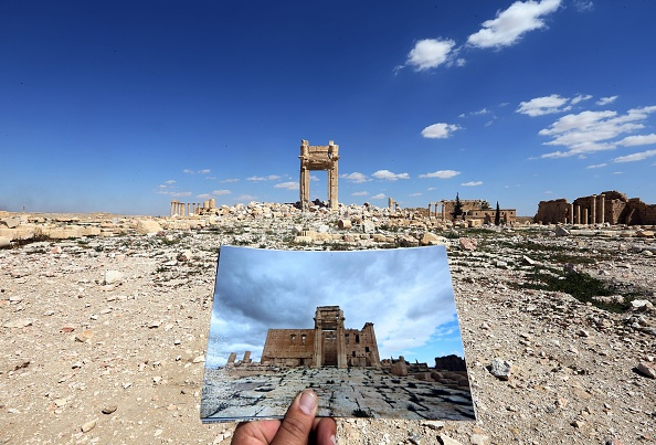 A general view taken on March 31, 2016 shows a photographer holding his picture of the Temple of Bel taken on March 14, 2014 in front of the remains of the historic temple after it was destroyed by Islamic State (IS) group jihadists in Sept. 2015 in the ancient Syrian city of Palmyra.