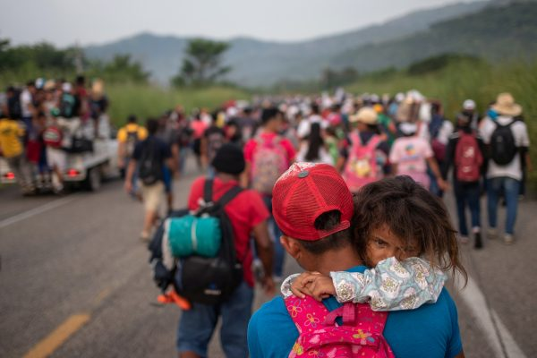 a man that is part of the migrant caravan carries his daughter