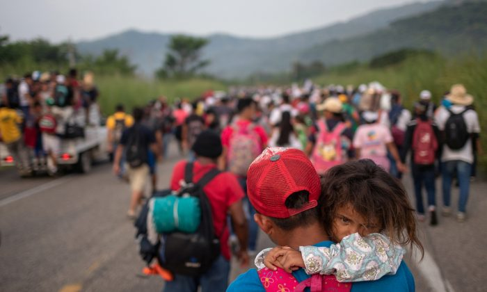 A man from Honduras carries his daughter Allison, 4, as he walks amid a caravan of thousands of migrants from Central America en route to the United States in the outskirts of Arriaga, Mexico, on Oct. 27, 2018. (Adrees Latif/Reuters)