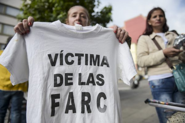 "A woman holds a T-shirt reading ""Victim of the FARC"" during a protest outside at the Special Jurisdiction for Peace."