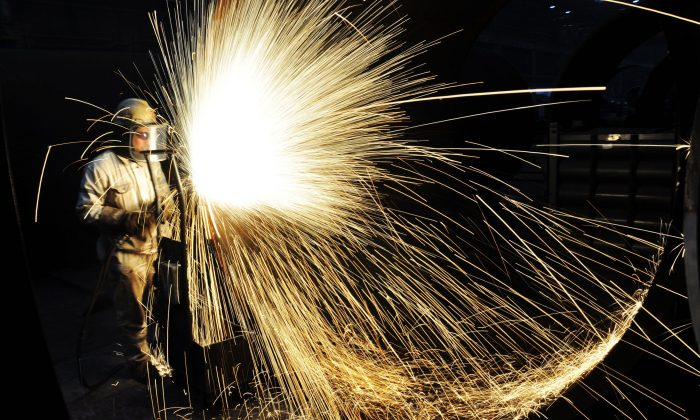 A Chinese worker cutting steel in Qingdao City, Shandong Province, China, on January 18, 2018. (AFP/Getty Images)